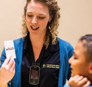 UCF Communications Disorders Student helps a young paitent pronounce the word which